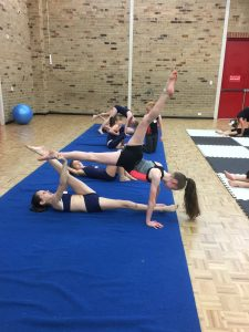 Dance students supporting each other to practice vertical splits