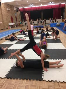 dance students paired off supporting straight leg lines in handstand