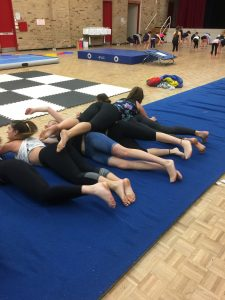 Acrobatic dance students in hall practicing tumbles